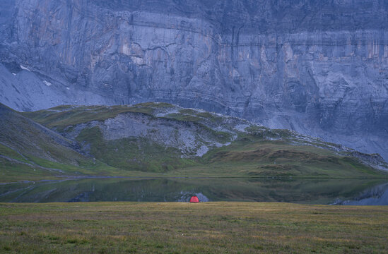 A single red tent at lake d'Anterne, France.