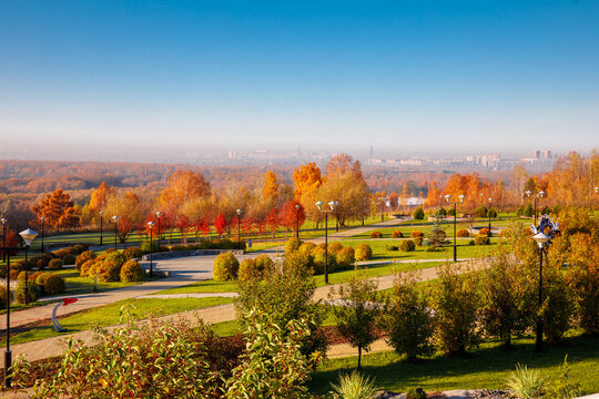 Top down photo in autumn showing the beautiful fall autumn colours of a park near Planetarium and city in fog on background in Novosibirsk