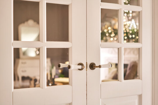 Beautiful modern door knob. Christmas lights on the background. Open, wooden front door from the interior of an upscale home with windows.