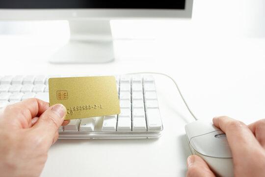クレジットカードを持ってネットショッピングをしている男性の手
