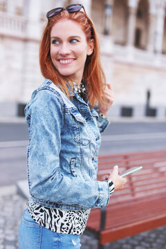 Cheerful redhead positive urban woman smiling and looking back
