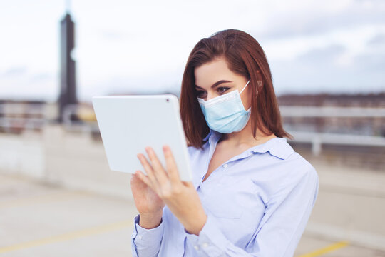 Young businesswoman in mask using digital tablet outdoors