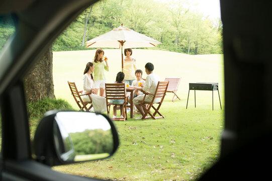 車から見た公園で食事する家族と友達