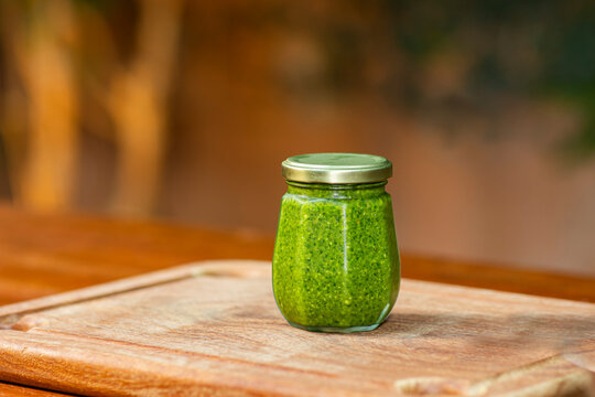 Natural seasoning. Bottle of pesto on the table.