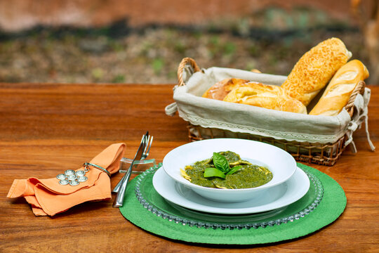 Plate with pesto ravioli. Wooden table with a breadbasket.