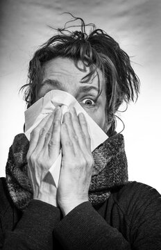 Portrait of a woman who has a cold. She wipes her nose with a handkerchief.