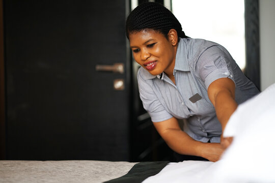 Portrait of African maid making bed in hotel room. Staff Maid Making Bed. African housekeeper making bed