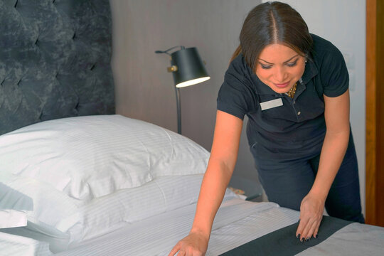 Portrait of woman maid making bed in hotel room. Housekeeper Making Bed