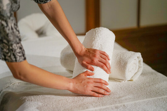 Woman hands on folds a towel, prepares a workplace in the spa for the reception of clients