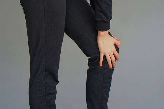 Pain In Knee. Close-up Female Leg With Painful Knees. Woman Feeling Joint Pain, Having Health Issues And Touching Leg With Hands. Body And Health Care Concept