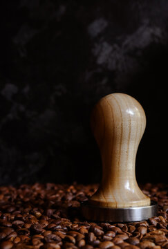 Fresh roasted coffee beans. Portafilter. Dark background. Tamper and coffee