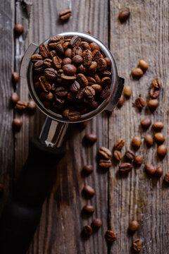 Fresh roasted coffee beans. Portafilter. Dark background.