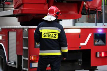 Fototapeta Funkcjonariusz straży pożarnej przy swoim samochodzie podczas akcji. obraz