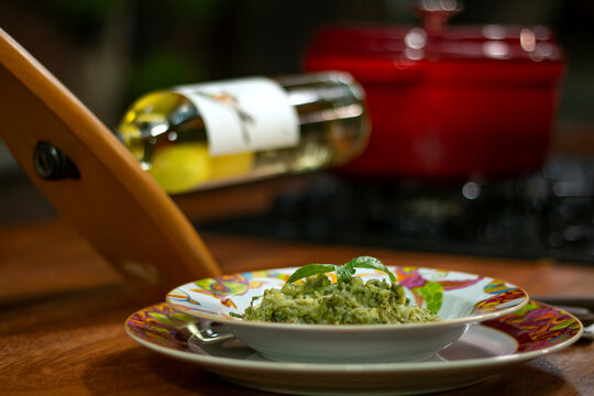 Colorful dish with pesto risotto. White wine and pot in the background.