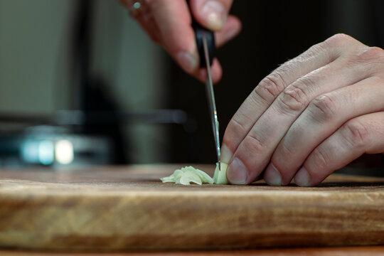 Chopping garlic on a wooden board for cooking. Copy space.