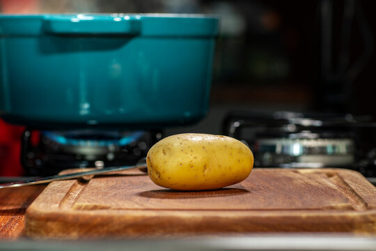 Raw potatoes on wooden board isolated. Defocused stove in the background with a pan.