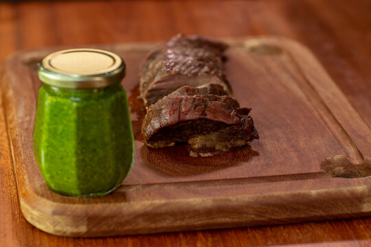 Grilled steak on a cutting board. Piece of filet mignon cut on a cutting board. Jar with fresh pesto sauce on the table.