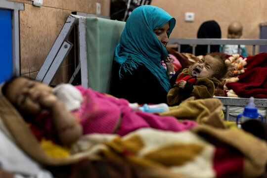 A mother holds her baby at the malnutrition ward of Indira Gandhi hospital in Kabul