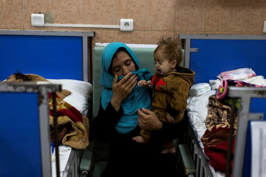 A mother carries her baby at the malnutrition ward of Indira Gandhi Children's hospital in Kabul