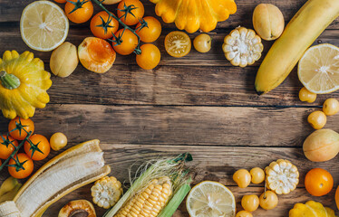 Various yellow and orange color fruits and vegetables on rustic wooden background. Food layout....