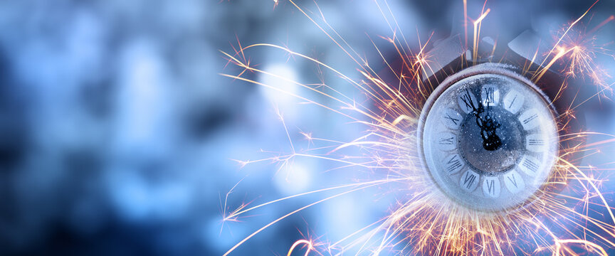 New year's eve countdown with alarm clock and sparklers on abstrakt dark blue bokeh background. Horizontal background for new year congratulations with space for text.