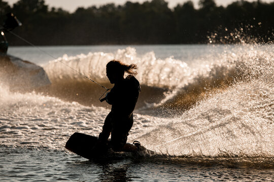 wet male wakeboarder holds taut rope and trying to stand on splashing wave.