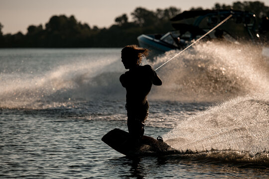 wakeboarder holds taut rope and ride trying to stand on splashing wave.