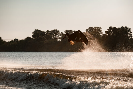 great view of active male wakeboarder making extreme stunts jumping and flips on wakeboard