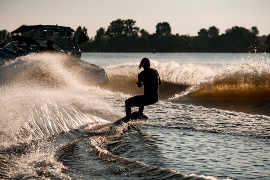 Rear view of man riding wakeboard behind motor boat on splashing river waves. Active and extreme sports
