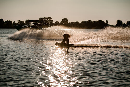 energy man holding rope and riding wakeboard and making trick behind motor boat on splashing river waves.