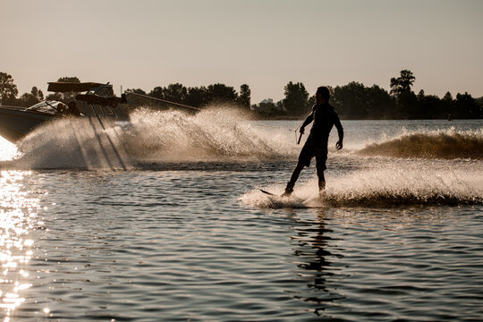 handsome man riding wakeboard behind motor boat on splashing river waves. Active and extreme sports