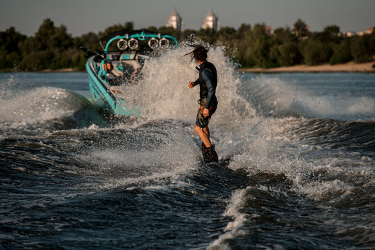 wet man riding wakeboard behind motor boat on splashing river waves. Active and extreme sports