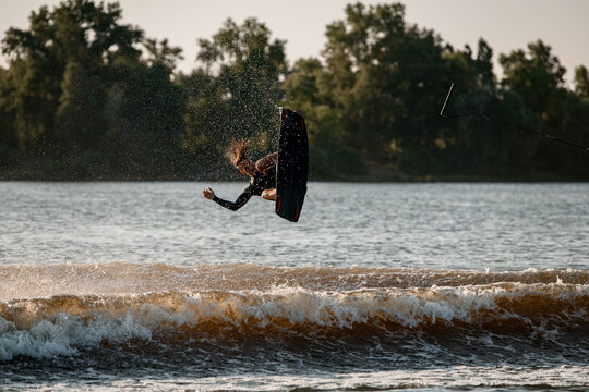 view of falling active male wakeboarder with wakeboard over water
