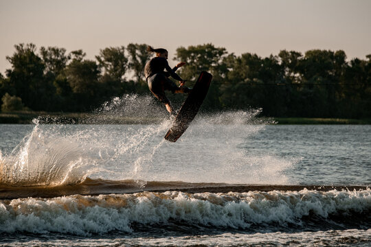 Great view of dynamic guy holding rope and jumping high with wakeboard over water