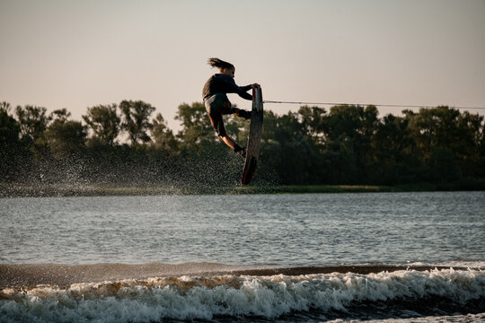 Magnificent view of energy man holding rope and jumping high on wakeboard