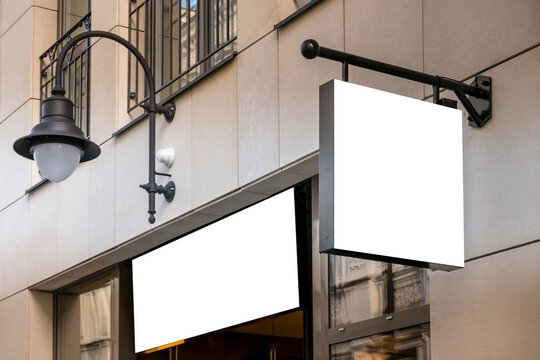 Mock up. Blank white rectangular shape signboard on the wall and above entrance outdoors. Signage of shop, store, cafe, restaurant
