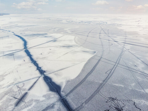 Aerial drone top view of snow covered frozen lake or river surface with big cracked ice diagonal lines. Natural winter landscape abstract texture pattern. Dangerous pond melting at thaw season