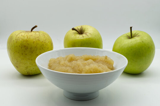 Apple sauce in a white bowl with raw apples on background. Apple puree and fresh green apples isolated on white background.