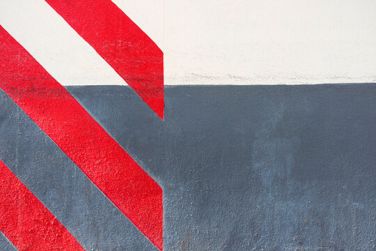 Abstract geometric wall texture background. Old white and gray color cement wall painted with diagonal red stripes
