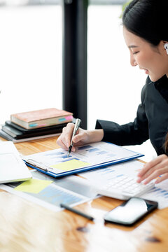 businesswoman hand writing and working with paperwork at office desk
