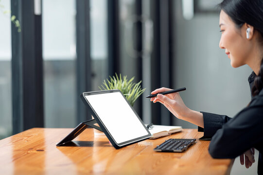 young asian woman using stylus pen working on tablet computer.