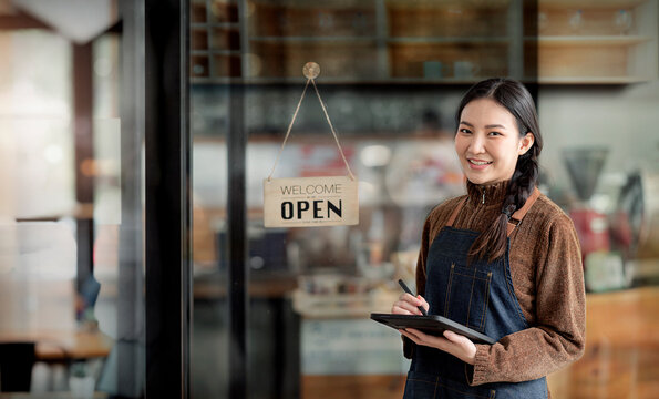 Beautiful asian young barista woman in apron holding tablet and standing in front of the door of cafe with open sign board.