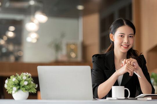 Young businesswoman smiling and looking at camra sitting at work.